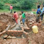 The Water Project: Mutao Community, Kenya Spring -  Kids Look On At Wall Construction