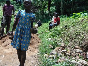 The Water Project:  Girl Carries Stones To The Construction Site