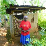 The Water Project: Ewamakhumbi Community, Mukungu Spring -  Woman In Front Of Latrine
