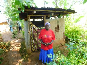 The Water Project:  Woman In Front Of Latrine