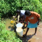 The Water Project: Kalenda A Community, Webo Simali Spring -  Community Members Fetching Water