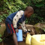 The Water Project: Mubinga Community, Mulutondo Spring -  A Child Fetching Water At The Unprotected Spring