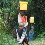 The Water Project: Mubinga Community, Mulutondo Spring -  A Family Carrying Water From The Spring