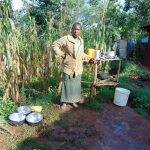 The Water Project: Rosterman Community, Lishenga Spring -  Woman Poses Next To Her Dish Rack