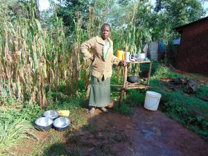 The Water Project:  Woman Poses Next To Her Dish Rack