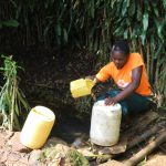 The Water Project: Imbinga Community, Imbinga Spring -  Agnes Fetching Water From The Spring