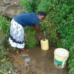 The Water Project: Buyangu Community, Mukhola Spring -  Beatrice Mukhola Fetching Water