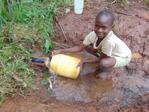 The Water Project:  Child Fills Container At Spring Pipe