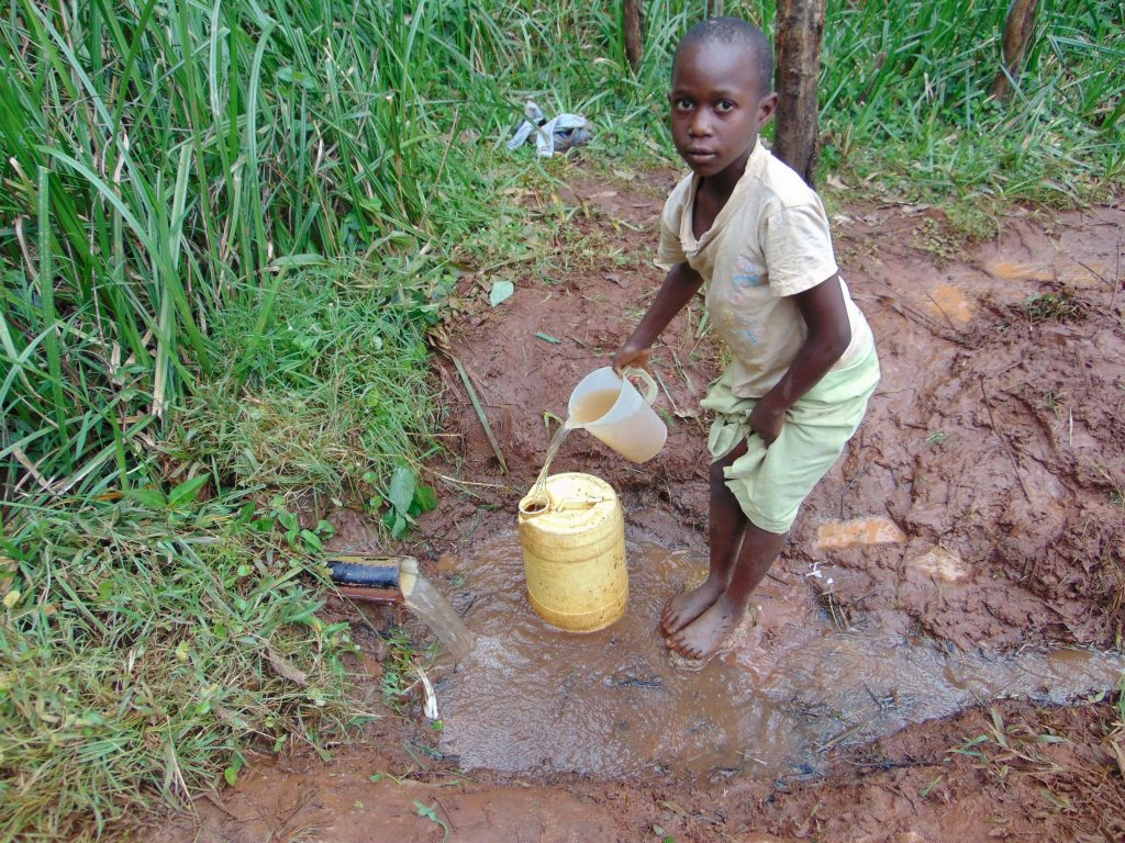 The Water Project : kenya19161-child-fills-container-with-water