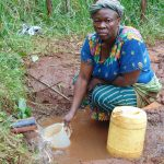 The Water Project: Masuveni Community, Masuveni Spring -  Scooping Water