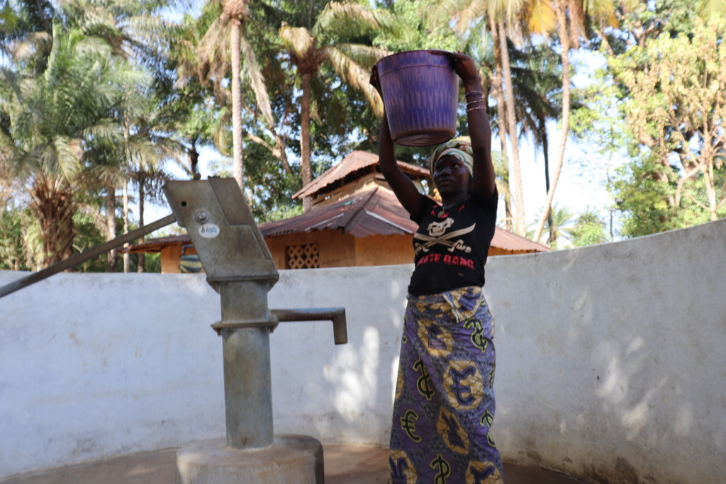The Water Project : sierraleone18251-community-member-helping-herself-with-a-contianer-of-water
