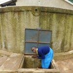 The Water Project: Emukangu Primary School, Shibuli -  Student Gets A Drink From The Rain Tank