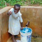 The Water Project: Chepnonochi Community, Chepnonochi Spring -  Sarah Edel Gives A Thumb Sup While Fetching Water