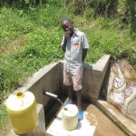 The Water Project: Emasera Community, Visenda Spring -  Joseph Musiomi Fetches Water