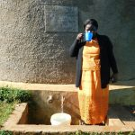 The Water Project: Eshikufu Primary School -  Head Teacher Mrs Emily Osundwa Drinks From The Rain Tank