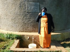 The Water Project:  Head Teacher Mrs Emily Osundwa Drinks From The Rain Tank