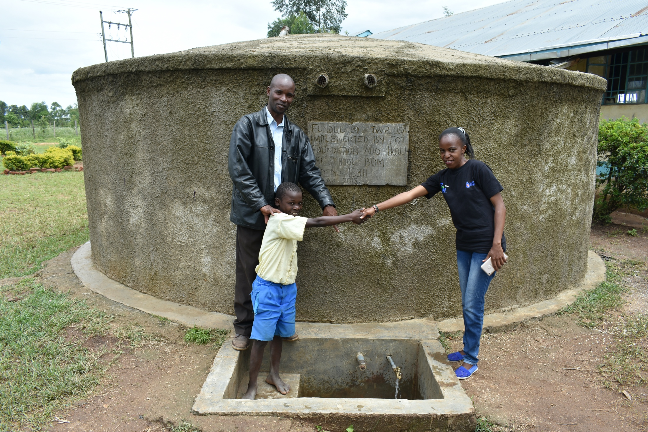The Water Project : 1-kenya18311-field-officer-betty-mwanji-shakes-hands-with-student-cheinster