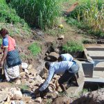 The Water Project: Shihungu Community, Shihungu Spring -  Backfilling With Stones