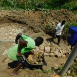 The Water Project: Ikonyero Community, Amkongo Spring -  Community Member Bringing Stones For Backfilling
