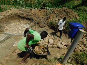 The Water Project:  Community Member Bringing Stones For Backfilling