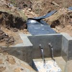 The Water Project: Sasala Community, Kasit Spring -  Backfilling With Plastic Tarp Added Clean Water Begins To Flow