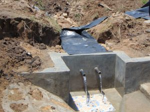 The Water Project:  Backfilling With Plastic Tarp Added Clean Water Begins To Flow