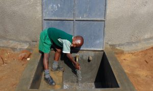 The Water Project:  Student Enjoying Water From The Rain Tank