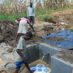 The Water Project: Shihungu Community, Shihungu Spring -  Backfilling With Plastic Tarp And Dirt