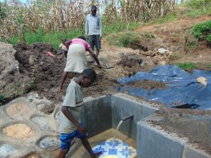 The Water Project:  Backfilling With Plastic Tarp And Dirt