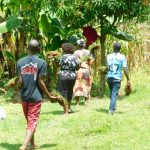 The Water Project: Ikonyero Community, Amkongo Spring -  Community Members Bringing Grass To Plant At The Spring