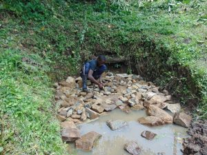 The Water Project:  Backfilling The Spring Box With Stones