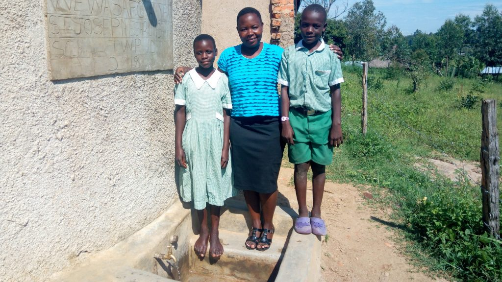 The Water Project : 2-kenya18077-field-officer-betty-majani-with-students-at-the-tank