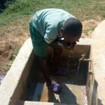 The Water Project: St. Joseph Eshirumba Primary School -  John Osaka Takes A Drink From The Rain Tank