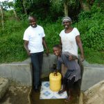 The Water Project: Muyundi Community, Baraza Spring -  Field Officer Jonathan Mutai With Jackline Baraza And Veline