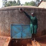 The Water Project: Isulu Primary School -  Noreen Reaches For The Pverflow Pipe
