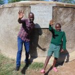 The Water Project: Mavusi Primary School -  Field Officer Victor Musemi With A Student At The Rain Tank