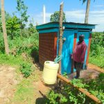 The Water Project: Koloch Community, Solomon Pendi Spring -  David Vidinyu With His Tippy Tap And Latrine Structure He Built Over His Sanitation Platform