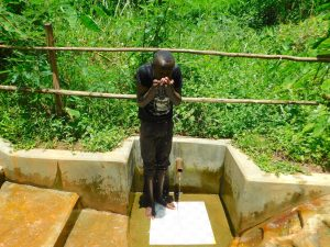 The Water Project:  Ivan Kibungei Lugaye Takes A Drink From The Spring