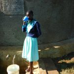 The Water Project: Eshikufu Primary School -  Vivian Osunya Drinks From The Rain Tank