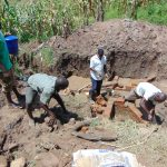 The Water Project: Shihungu Community, Shihungu Spring -  Community Members Help Lay Bricks