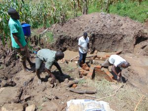 The Water Project:  Community Members Help Lay Bricks