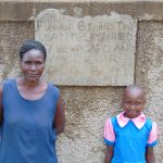 The Water Project: Kapsotik Primary School -  Staff Member With Sheila In Front Of Rain Tank