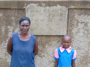 The Water Project:  Staff Member With Sheila In Front Of Rain Tank