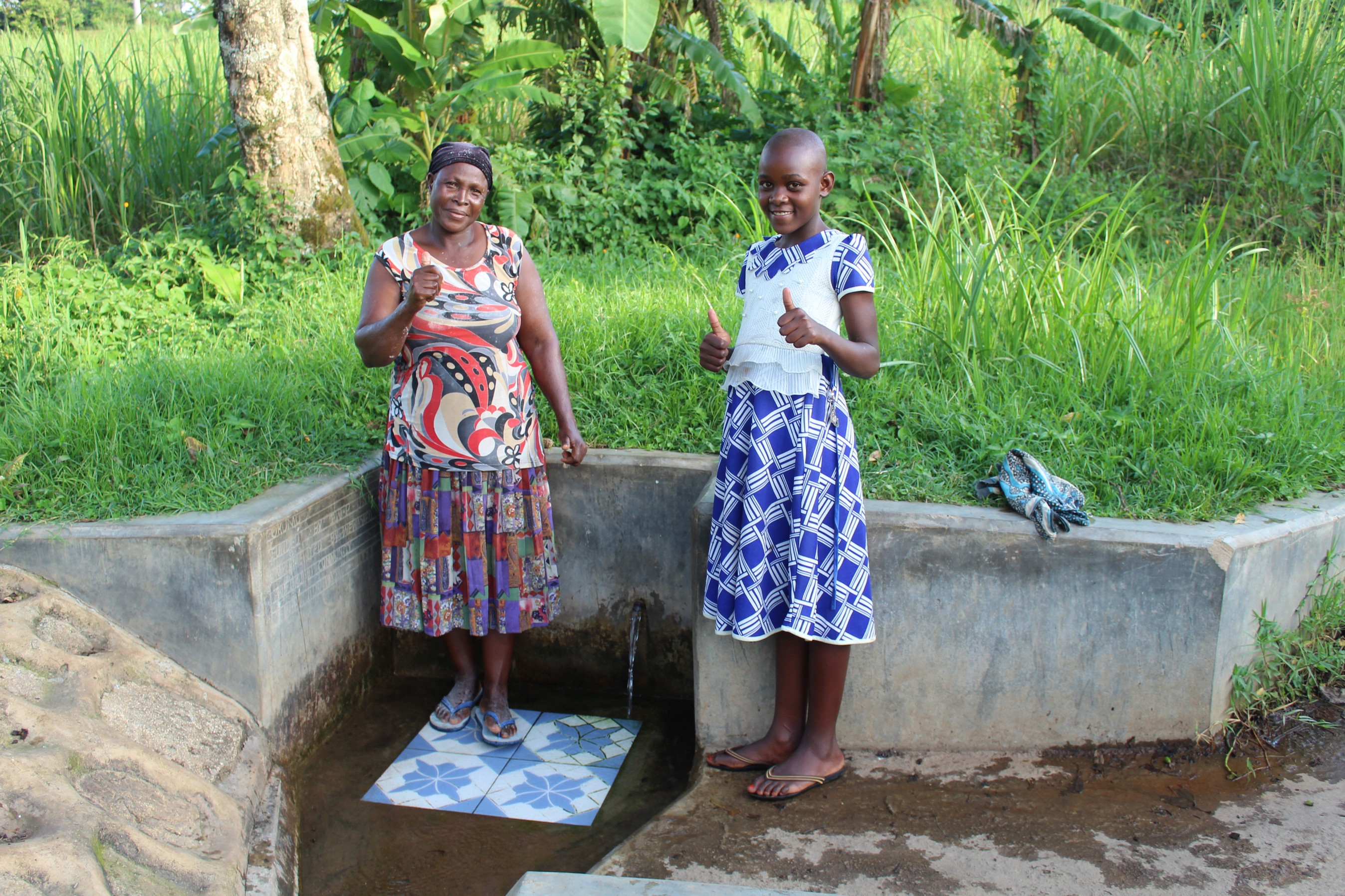The Water Project : 4-kenya18129-felistus-and-lucy-give-thumbs-up-for-clean-water