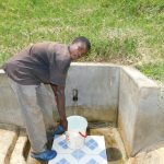 The Water Project: Emachembe Community, Mukabane Spring -  Dennis Ommollo Fetches Water