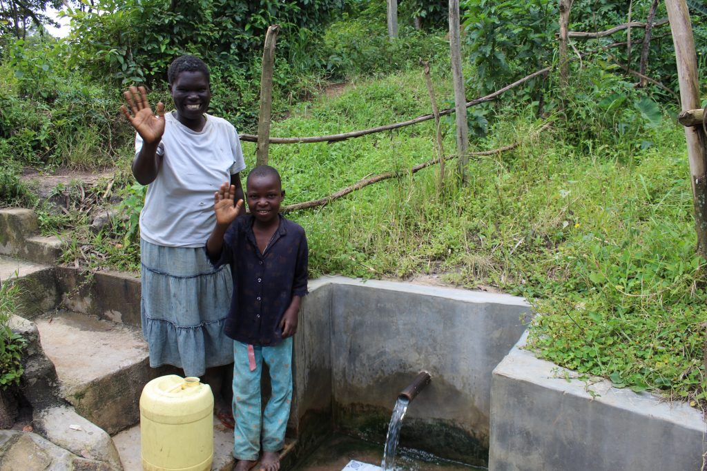 The Water Project : 4-kenya18144-hellen-and-robinson-wave-from-the-spring