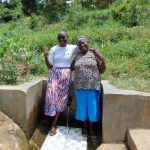 The Water Project: Emaka Community, Ateka Spring -  Mary With Field Officer Joan Were