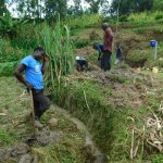 The Water Project: Ikonyero Community, Amkongo Spring -  Digging Drainage For Spring Water