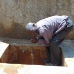 The Water Project: Madegwa Primary School -  Mr Lukao Drinks From The Rain Tank