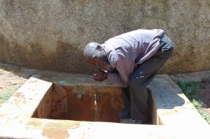 The Water Project:  Mr Lukao Drinks From The Rain Tank
